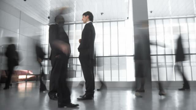 hd-zeitraffer: geschäftsleute, die diskussion im geschäftigen korridor - zeitraffer fast motion stock-videos und b-roll-filmmaterial