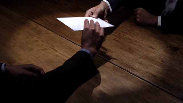 Businessmen in dark room accepting payoff in envelope in deal