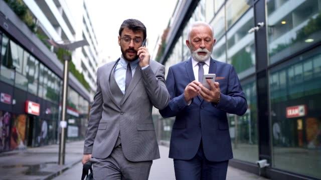 仕事後の散歩中に携帯電話で占領されたビジネスマン ビデオ