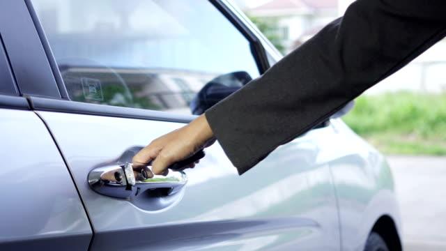 stockvideo's en b-roll-footage met zakenlieden druk op de afstandsbediening om de auto te ontgrendelen en de deur open. - ver