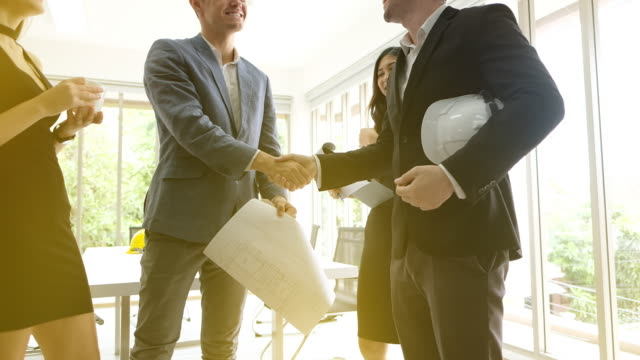 businessmen shaking hands in a corporate office,handshake of two businesspeople standing talk in office, agreement, partnership,with hand held video - fiducia video stock e b–roll