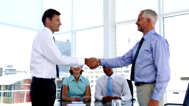 Businessmen shaking hands in the meeting room video