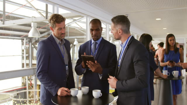 Businessmen talking during a coffee break at a convention Front view of two young Caucasian businessmen and a young African American businessman talking, looking at a tablet  computer and drinking coffee during a break at a business conference. In the background a diverse group of business delegates can be seen talking event stock videos & royalty-free footage