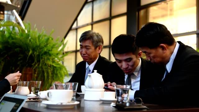 カフェのテーブルで幸せな同僚とビジネスマン - お茶の時間点の映像素材/bロール