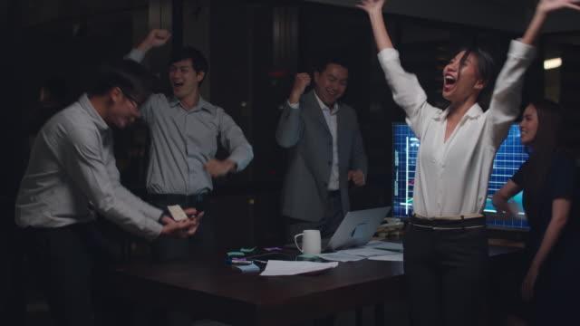 ビジネスマンアジアは、市内の夜間オフィスの会議室で成功した後の成果の幸せを感じる文書を投げる。 - 応援点の映像素材/bロール