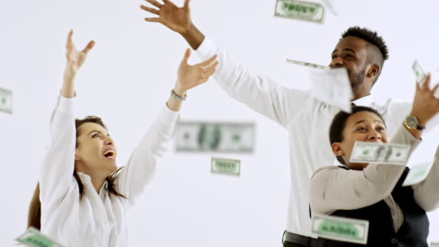 Businesspeople Catching Cash Falling from Above Studio shot with white background: happy black multi-ethnic group of businesspeople laughing and catching money falling on them from above catching stock videos & royalty-free footage