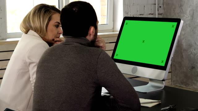 stockvideo's en b-roll-footage met ondernemers samen werken een desktopcomputer informatie op kantoor te vergelijken. groen scherm mock-up display - e mail