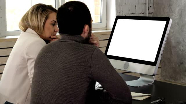 stockvideo's en b-roll-footage met ondernemers samen werken een desktopcomputer informatie op kantoor te vergelijken. witte display - e mail