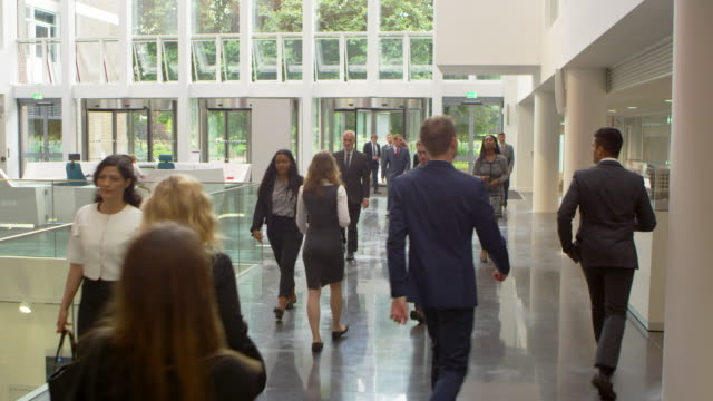 businesspeople in busy lobby area of modern office shot on r3d - hotel checkin video stock e b–roll