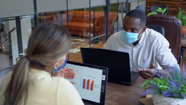 Businesspeople in office working with protective face masks, COVID-19 virus