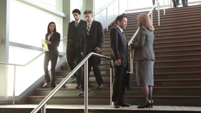 uomini d'affari incontro sulle fasi della hall - 20 o più secondi video stock e b–roll