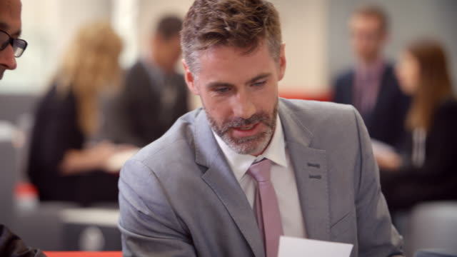 Businesspeople Meeting In Busy Lobby Of Modern Office video