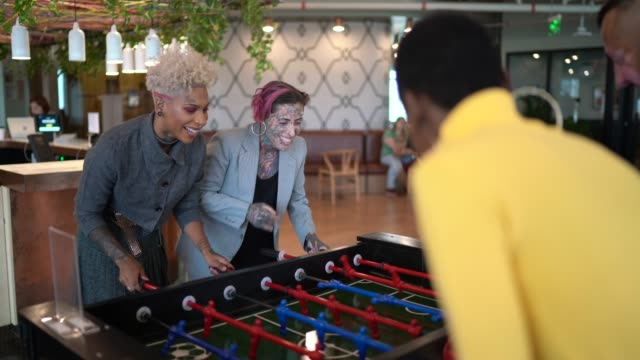Businesspeople playing foosball at coworking