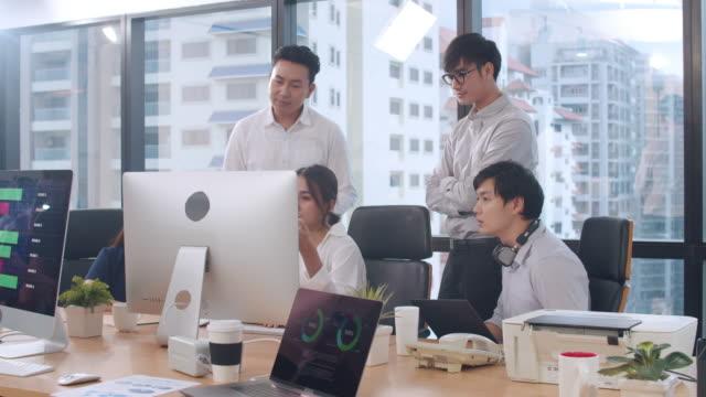 コンピュータプレゼンテーションとコミュニケーション会議を使用するビジネスマンは、現代のオフィスで計画の成功戦略を計画するプロジェクトの同僚についてのアイデアをブレーンスト� - クリエイティブな職業点の映像素材/bロール