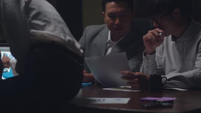 stockvideo's en b-roll-footage met zakenmensen die laptoppresentatie en communicatievergadering gebruiken brainstormen over nieuwe projectcollega's die in night office een successtrategie plannen. - oost azië