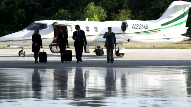 Businesspeople walking to corporate jet video
