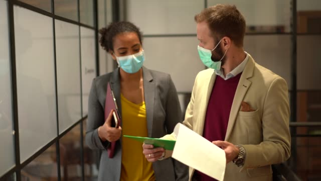 Businesspeople wearing face masks at work during COVID-19 pandemic Businesspeople wearing masks in the office for illness prevention during COVID-19 pandemic occupational safety and health stock videos & royalty-free footage