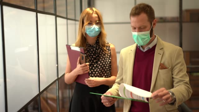 businesspeople wearing face masks at work during covid-19 pandemic - virus protection video stock e b–roll