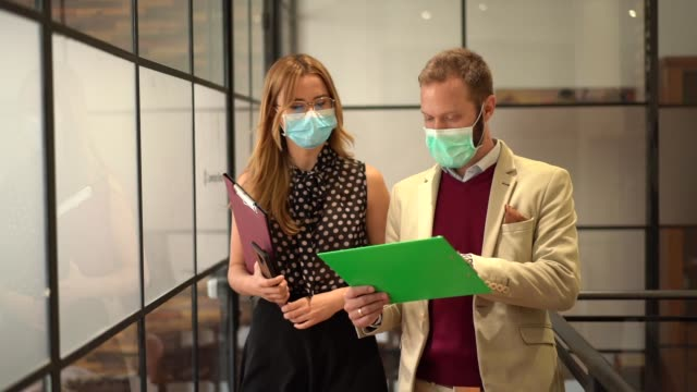 businesspeople wearing face masks at work during covid-19 pandemic - businessman covid mask video stock e b–roll