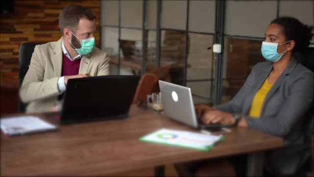 businesspeople with face masks in the office during covid-19 pandemic - businessman covid mask video stock e b–roll