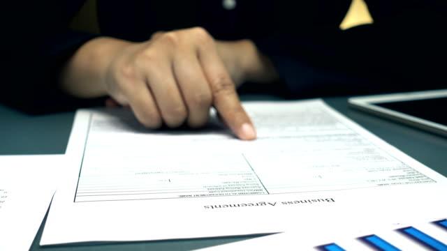 stockvideo's en b-roll-footage met ondernemer is business-overeenkomst lezen en werken op kantoor - bord bericht