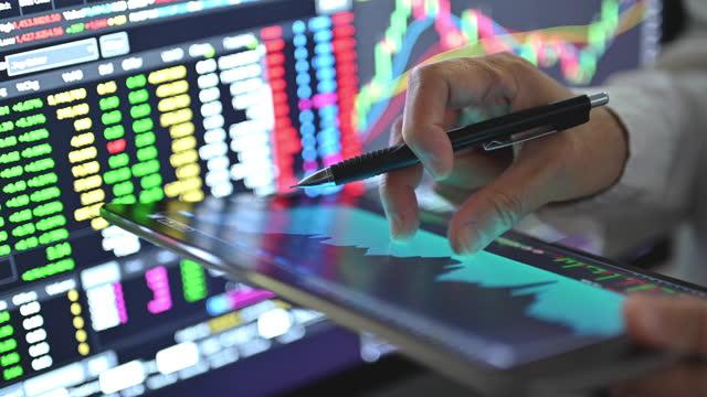 stockvideo's en b-roll-footage met businesssman met behulp van grafiek en grafiek om de handel in aandelen en cryptogeld na blobal businesss naar bullmarket na recessie - bitcoin