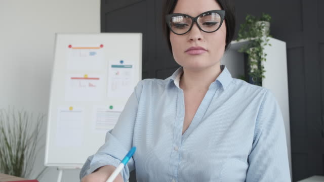 Businesswoman analyzing documents at office video
