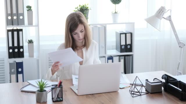 オフィスで文書を分析するビジネスウーマン - ファイル点の映像素材/bロール