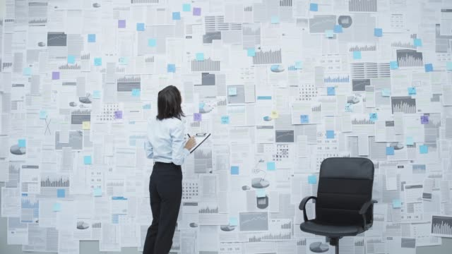 vidéos et rushes de femme d'affaires analysant des données financières sur un mur - bloc note