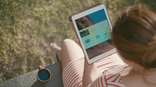 vídeos de stock e filmes b-roll de businesswoman analyzing market data information on a digital tablet in public park,slow motion - utensílio
