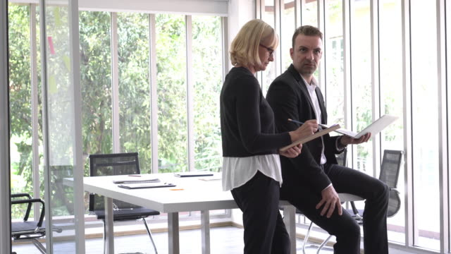 geschäftsfrau und geschäftsmann diskutieren gemeinsam - formelle geschäftskleidung stock-videos und b-roll-filmmaterial
