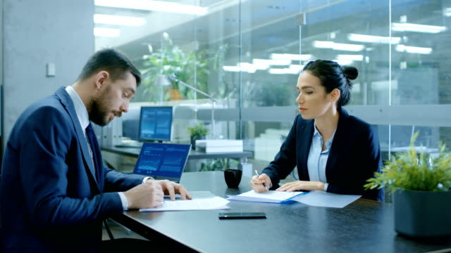 businesswoman and businessman have conversation. draw up a contract, filling papers in conference room. in the background modern bright office with glass walls. - firma video stock e b–roll