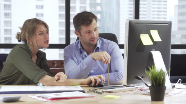 Businesswoman and businessman sitting at the desk and pointing at desktop computer for discussing business in the modern high rise office, Brainstorming, Solving Problems, Pan shot