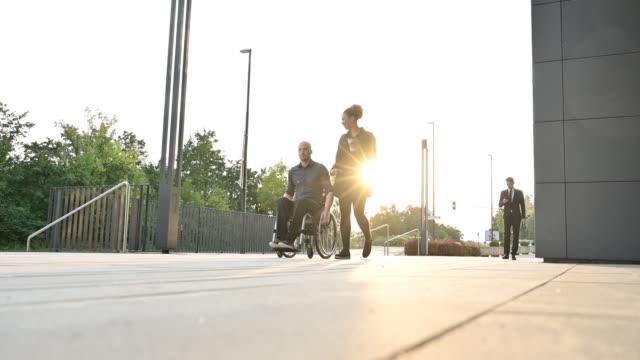 vídeos y material grabado en eventos de stock de empresaria y colega en silla de ruedas viajando al trabajo - posición descriptiva