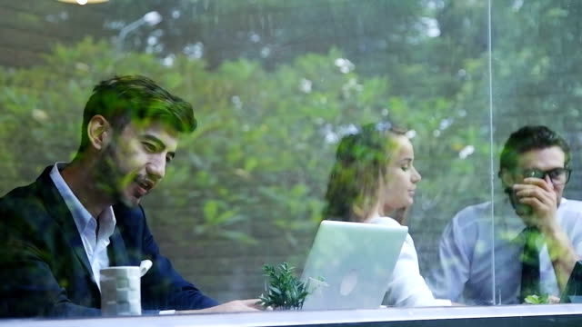 businesswoman and man having discussion. While drinking coffee at lunch break. video