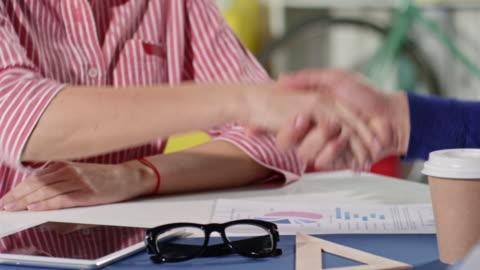 imprenditrice e partner che stringono la mano - abbigliamento casual video stock e b–roll