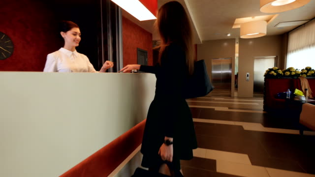 Businesswoman arrives to the hotel at the reception and get a key. 4K. video