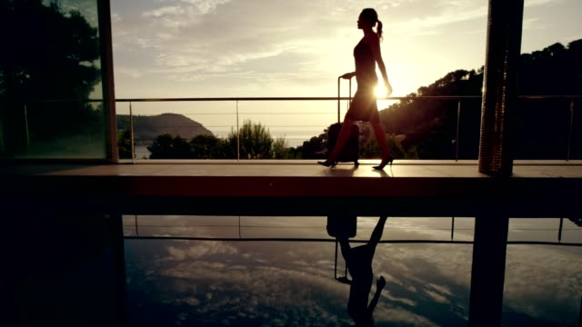 Businesswoman arriving to a luxurious spa. Woman with suitcase walking along the pool. Luxurious hotel hotel stock videos & royalty-free footage