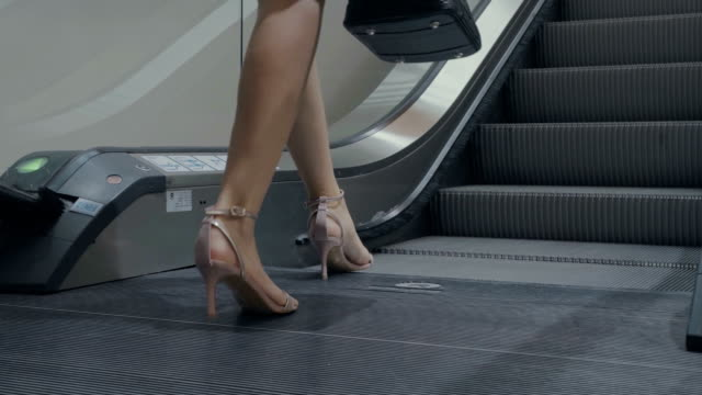 businesswoman ascending escalator in office building - escalator video stock e b–roll
