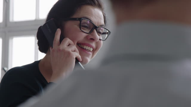 Businesswoman at her workplace talking on the landline phone Businesswoman talking on the landline phone and smiling in the office. Female professional using phone while working at her desk. landline phone stock videos & royalty-free footage