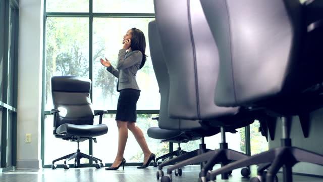 Businesswoman boardroom talking on phone, pacing
