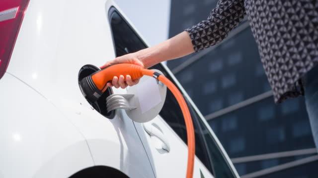 金融街に事務所の前で電気自動車を充電する実業家 - 電気自動車点の映像素材/bロール