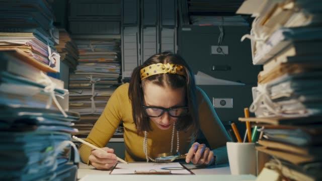 geschäftsfrau überprüft ein dokument mit einer lupe - lupe stock-videos und b-roll-filmmaterial
