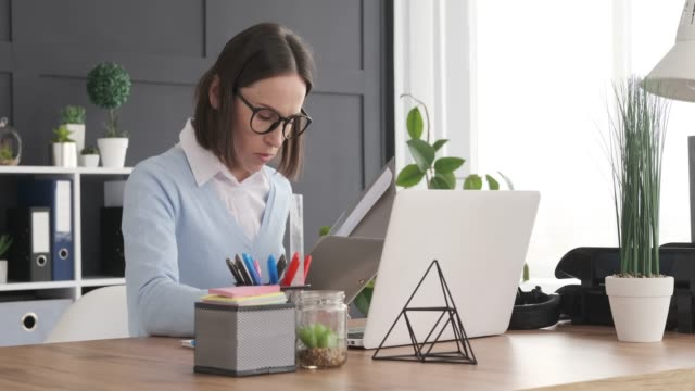 Businesswoman checking documents while working on laptop