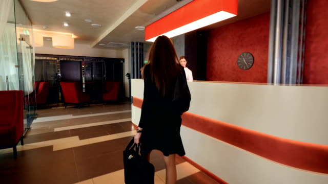 Businesswoman checking in at a reception desk. 4K. Businesswoman checking in at a reception desk. checkout stock videos & royalty-free footage