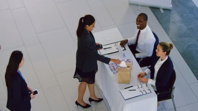 vídeos y material grabado en eventos de stock de mujer empresaria que se registra en la mesa de registro de la conferencia 4k - register