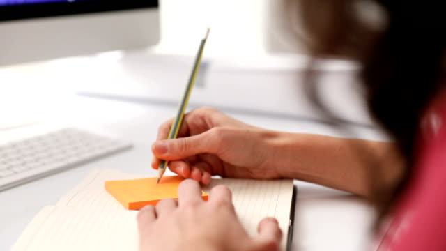 Businesswoman checking notes and post it video