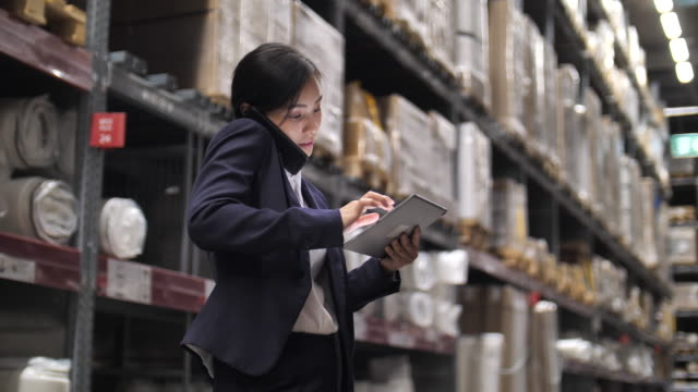 Businesswoman Checking order Stock Using Digital Tablet In Distribution Warehouse