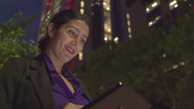 Businesswoman checking the digital tablet in the street at night video