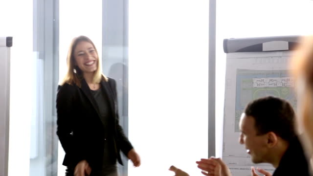 Businesswoman clapping with her team at the end of a meeting video